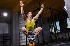 Jeune homme sportif faisant des exercices dans le gymnase convenable de croix tout en se tapissant sur deux jambes sur le kettleb photo stock