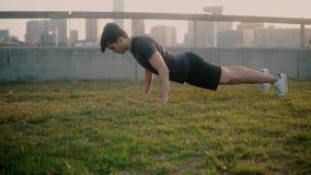 Jeune homme sportif faisant des exercices de pompes au parc clips vidéos