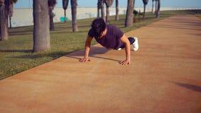 Jeune homme sportif faisant des exercices de pompes au parc banque de vidéos