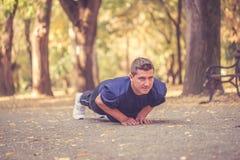 Jeune homme sportif faisant des pousées dehors photographie stock