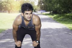 Jeune homme sportif faisant une pause pendant pulser provocant extérieur image libre de droits