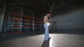 Jeune homme sportif jouant sur le berimbau brésilien national d'instrument après avoir fait des éléments de capoeira dans la cham banque de vidéos