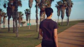 Jeune homme sportif marchant au parc de palmier près de la plage banque de vidéos