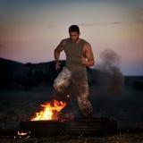 Jeune homme sportif s'exerçant sur le champ poussiéreux Photo stock