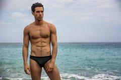 Jeune homme sportif sans chemise se tenant dans l'eau à côté du rivage d'océan Photos libres de droits
