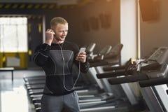 Jeune homme sportif sur le tapis roulant dans le centre de fitness photo stock