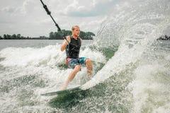 Jeune homme sportif wakesurfing sur le conseil tenant un câble image libre de droits