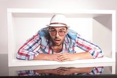 Jeune homme stupéfait de mode se trouvant à l'intérieur d'un boîtier blanc Image libre de droits