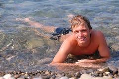 Jeune homme sur la plage Photo stock