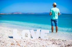 Jeune homme sur la plage avec amour de mot Image stock