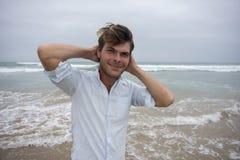 Jeune homme sur la plage avec des bras derrière la tête Photographie stock