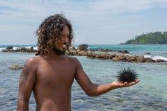 Jeune homme sur la plage tenant l'oursin dans sa main Photos libres de droits