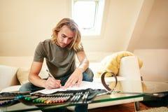 Jeune homme sur le divan, dessinant dans livre de coloriage Images stock