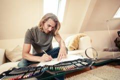 Jeune homme sur le divan, dessinant dans livre de coloriage Photographie stock