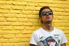 Jeune homme sur le fond du mur de briques jaune Images libres de droits