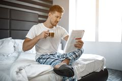 Jeune homme sur le lit pendant le matin Il reposent et ont lu la tasse de prise de type de journal de café Gentil et gai photos stock