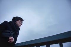 Jeune homme sur le pont, sur le fond du ciel nuageux Images stock