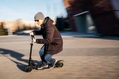 Jeune homme sur le scooter électrique sur la rue photographie stock