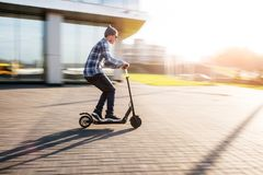 Jeune homme sur le scooter électrique sur la rue photo stock