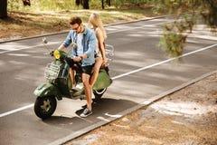 Jeune homme sur le scooter avec l'amie dehors Images stock