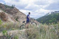 Jeune homme sur le vélo de montagne dans les montagnes Images stock