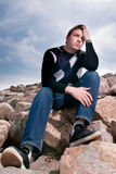 Jeune homme sur les roches en nuages Image stock