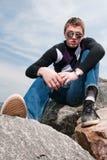 Jeune homme sur les roches en nuages dans les lunettes Photographie stock libre de droits