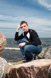 Jeune homme sur les roches sur la mer Photo stock
