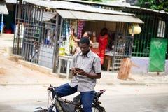 Jeune homme sur un vélo avec un téléphone portable à disposition images stock