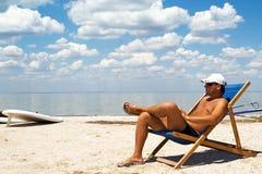Jeune homme sur une présidence sur une plage Image stock