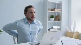 Jeune homme surchargé sentant le dos physique de malaise dedans banque de vidéos
