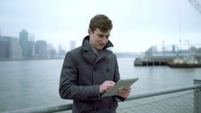 Jeune homme surfant l'Internet sur son PC de comprimé près du fleuve Hudson avec l'île de Manhatan derrière lui banque de vidéos