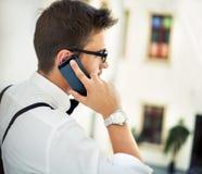 Jeune homme talling au téléphone portable Photo stock