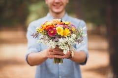 Jeune homme tenant des fleurs dans la chemise bleue et les shorts Forêt conifére sur un fond Belles fleurs d'automne photos libres de droits