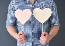 Jeune homme tenant deux coeurs Le jour de Valentine Photo libre de droits