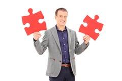 Jeune homme tenant deux morceaux de puzzle Photo stock