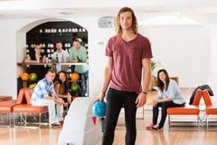 Jeune homme tenant la boule dans le bowling au club Photographie stock libre de droits