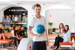 Jeune homme tenant la boule de bowling bleue dans le club Image libre de droits