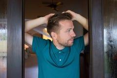 Jeune homme tenant la fenêtre proche pendant le matin et regardant loin Photo stock