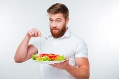 Jeune homme tenant la fourchette pour manger le repas de salade de légume frais image stock