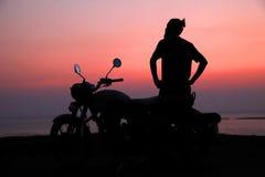 Jeune homme tenant la motocyclette proche et appréciant la vue de coucher du soleil Images libres de droits