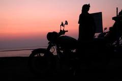 Jeune homme tenant la motocyclette proche et appréciant la vue de coucher du soleil Image libre de droits