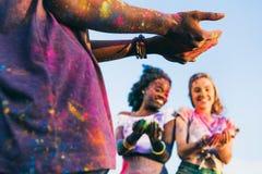 Jeune homme tenant la poudre colorée tandis que filles multi-ethniques gaies se tenant derrière au festival de holi Images stock