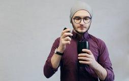 Jeune homme tenant la tasse thermo noire avec du café aromatique, au-dessus du fond texturisé blanc photo stock