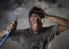 Jeune homme tenant le câble fumant après accident électrique avec le visage brûlé sale dans l'expression triste drôle Photo stock