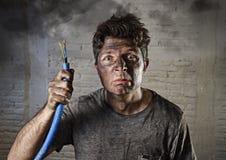 Jeune homme tenant le câble fumant après accident électrique avec le visage brûlé sale dans l'expression triste drôle Photos libres de droits