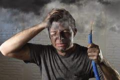 Jeune homme tenant le câble fumant après accident électrique avec le visage brûlé sale dans l'expression triste drôle Image stock
