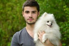 Jeune homme tenant le chiot allemand de spitz photographie stock libre de droits