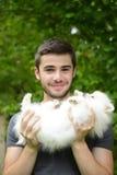 Jeune homme tenant le chiot allemand de spitz photographie stock