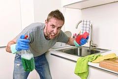 Jeune homme tenant le jet détersif de nettoyage et éponge lavant fâché propre de cuisine à la maison dans l'effort photos stock